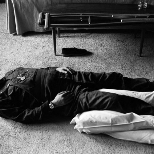 May, 1973: Poet Allen Ginsberg, with a broken leg, lies on the floor meditating. By Tony Barnard.